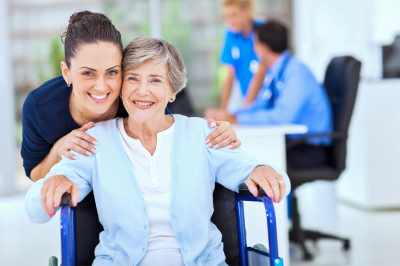 Caring adult daughter accompanying senior mother visiting doctor