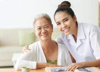 elderly woman and caregiver smiling together
